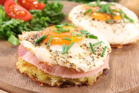 browns: Potato pancakes with ham, egg, pepper, chives and fresh salad Stock Photo