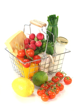 Shopping cart with milk, cheese and mixed vegetables