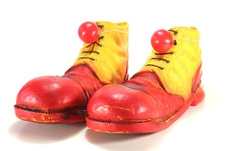 payaso: zapatos de payaso rojo y amarillo con narices de payaso rojo sobre fondo blanco
