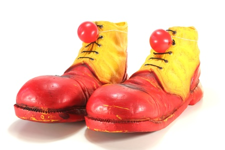 red and yellow clown shoes with red clown noses on white background