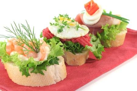 Canape with lettuce, ham, steak tartare, shrimp and quail eggs on a white background photo