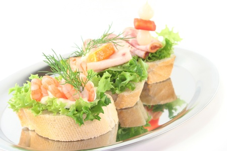Canape with lettuce, shrimps, sausage and vegetables on a white background