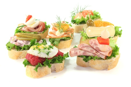 Canape with lettuce, cheese, sausage and eggs on a white background