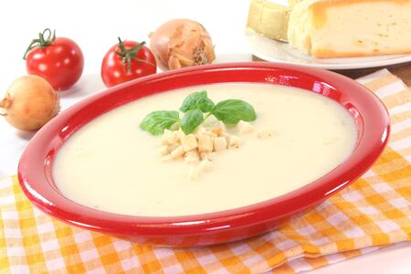 croutons: Cheese cream soup with tomato, Croutons and basil on a white background