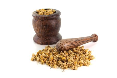 remedies: dried chamomile flowers with a mortar on a white background Stock Photo