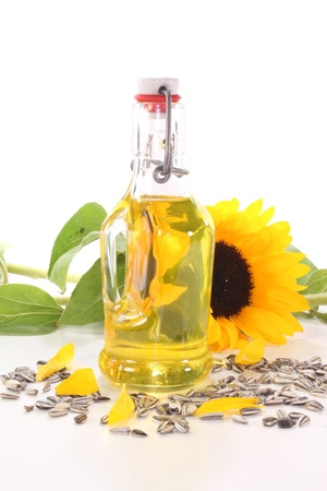 semillas de girasol: Aceite de girasol con girasoles y semillas de girasol sobre un fondo blanco