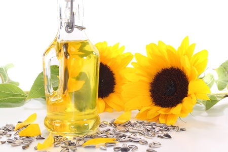 aceite de cocina: Aceite de girasol con girasoles y semillas de girasol sobre un fondo blanco