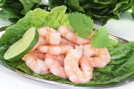 fresh shrimp with lime, lemon balm and lettuce on a silver platter before white background photo