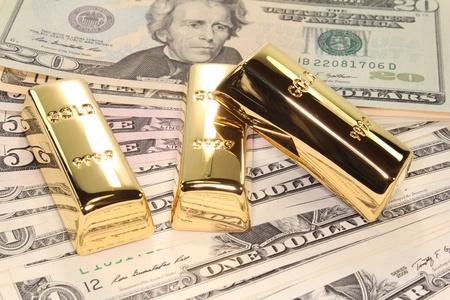 bullion: three large gold bars at many dollar bills Stock Photo