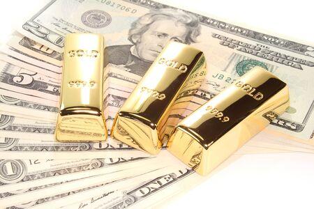 three large gold bars at many dollar bills photo