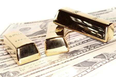 three large gold bullion at many dollar bills photo