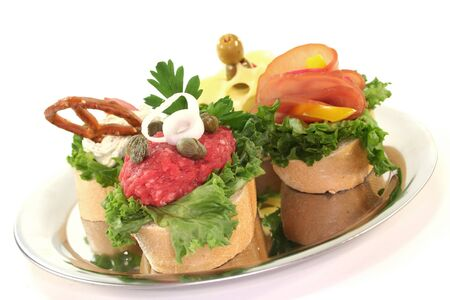 garnishing: Canape with lettuce, cheese, sausage, cream cheese and tartare on a white background