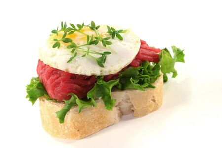 garnishing: Canape with lettuce, Tartare, fried egg and watercress on a white background