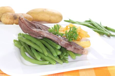 frites: Lamb meat with pommes frites and green beans on a white background