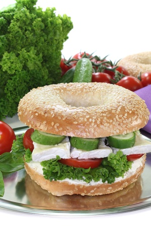 bagel: Bagel with Camembert cheese, tomato, cucumber, cream cheese and lettuce on white background