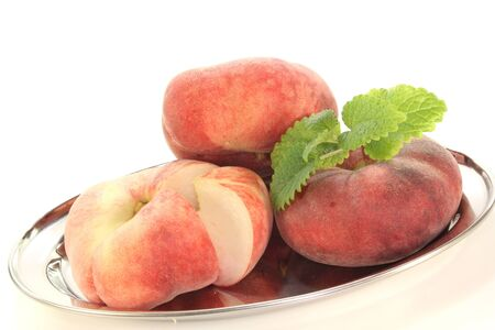 three mountain peaches on a platter with lemon balm on a white background photo