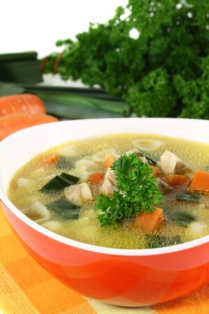 chicken soup: Chicken soup with vegetables and parsley in a bowl