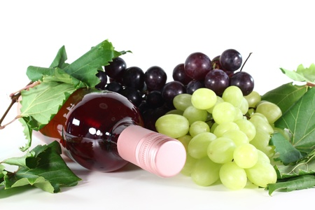 a bottle of rose wine, grapes and vine tendril on a white background photo