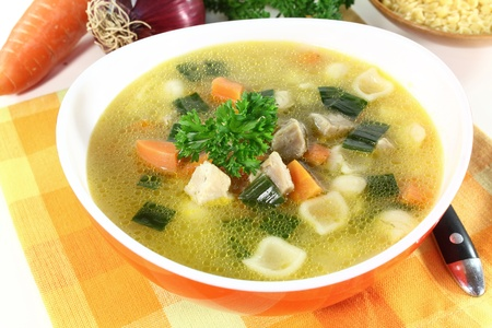 broth: Chicken soup with vegetables and parsley in a bowl