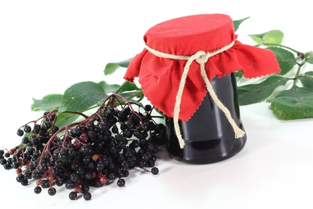 Elderberry jelly with elderflower berries and leaves on a white background Stockfoto