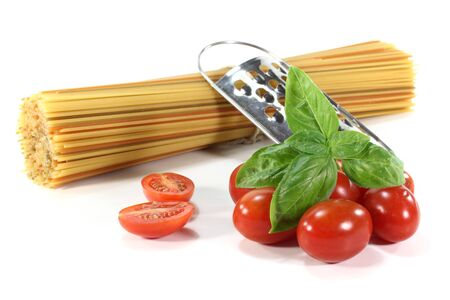 bunch of colorful spaghetti with tomatoes and basil on a white background Stock Photo