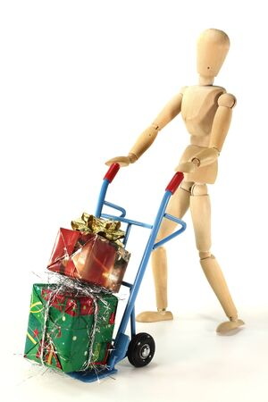 sack truck: many colorful Christmas presents on a hand truck with wooden figure Stock Photo