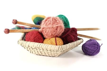 wool fiber: bolas de colores de la lana con agujas de tejer en una cesta Foto de archivo