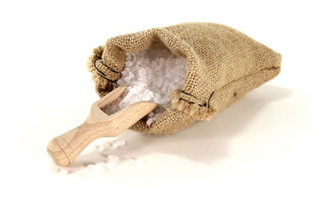 Salzkörner auf einem Scheffel mit Meersalz in der Tasche