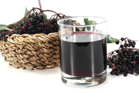 Holundersaft mit Holunder Beeren und Blätter auf weißem Hintergrund Lizenzfreie Bilder