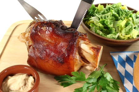 hock: Pork hock with mustard, lettuce and parsley on a board with cutlery