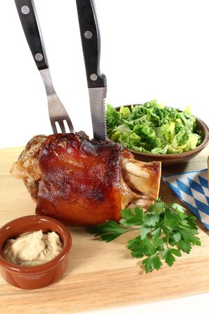 hock: fresh Pork hock with mustard, lettuce and parsley on a board with cutlery Stock Photo