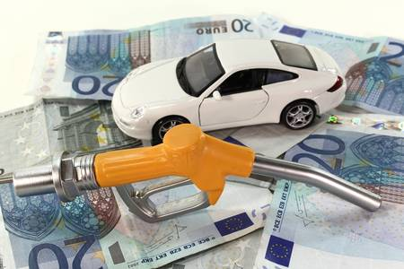 Petrol pump nozzle with a car on a pile of euro notes photo