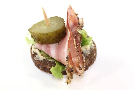Pumpernickel bread with lettuce, smoked bacon and pickled cucumber photo
