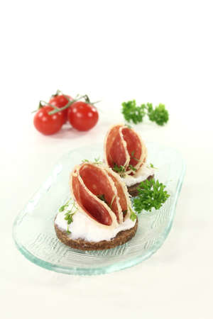 pumpernickel: Pumpernickel bread with cream cheese, salami and garden cress on a glass bowl Stock Photo