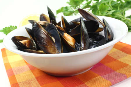 fresh steamed mussels in a white bowl with napkin photo