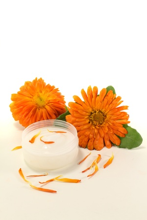ointment: Calendula ointment with marigold flowers, leaves and petals on a light background
