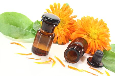 tincture: Marigold tincture with calendula flowers and leaves on a light background