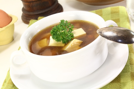 repast: Beef consomme with greens, egg and fresh parsley Stock Photo