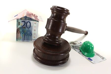 Labour law - Gavel with house and construction helmet photo