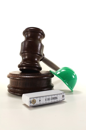 Labour - Gavel with house, construction helmet and ruler on a bright background photo