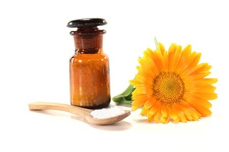 Homeopathy globules, an apothecary jar and marigold Stockfoto