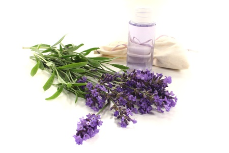 Lavender oil with Lavender bag and fresh lilac flowers on a bright background photo