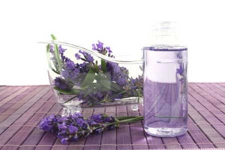 Lavender oil before a bath with flowers and leaves on bright background photo