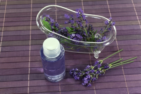 Lavender oil before a bath with flowers and leaves on violet background photo