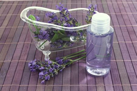 Lavender oil before a bath with flowers and leaves on purple background photo