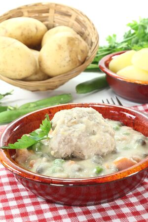 delicious cooked meatballs in a white sauce with capers, garlic and parsley photo