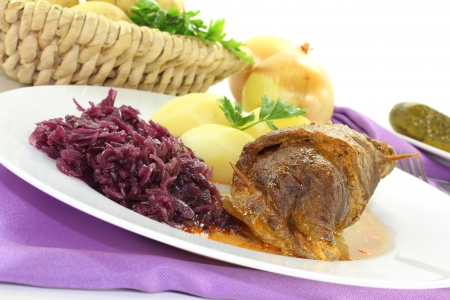 stuffed Beef roulade with potatoes and red cabbage on a bright background