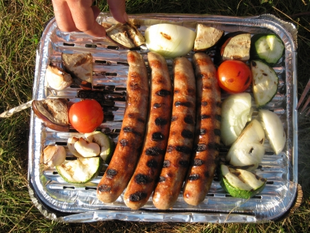 Hands on a disposable barbecue with sausages, onions and vegetables photo