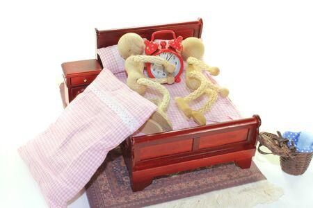 Sleep - two wooden doll and alarm clock in bed with bedside table and plaid bedding Stock Photo