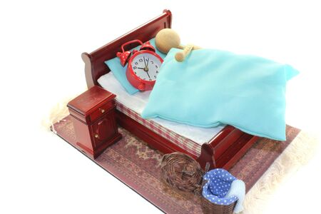 arousing: Sleep - a wooden doll and alarm clock in bed with bedside table and blue bedding Stock Photo